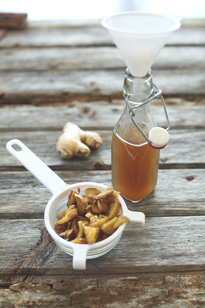 Jar of ginger syrup with a funnel resting on it and pieces of strained ginger