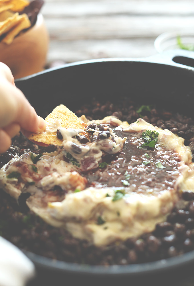 Using a chip to scoop up a bite of our Black Bean Raspberry Chipotle Dip