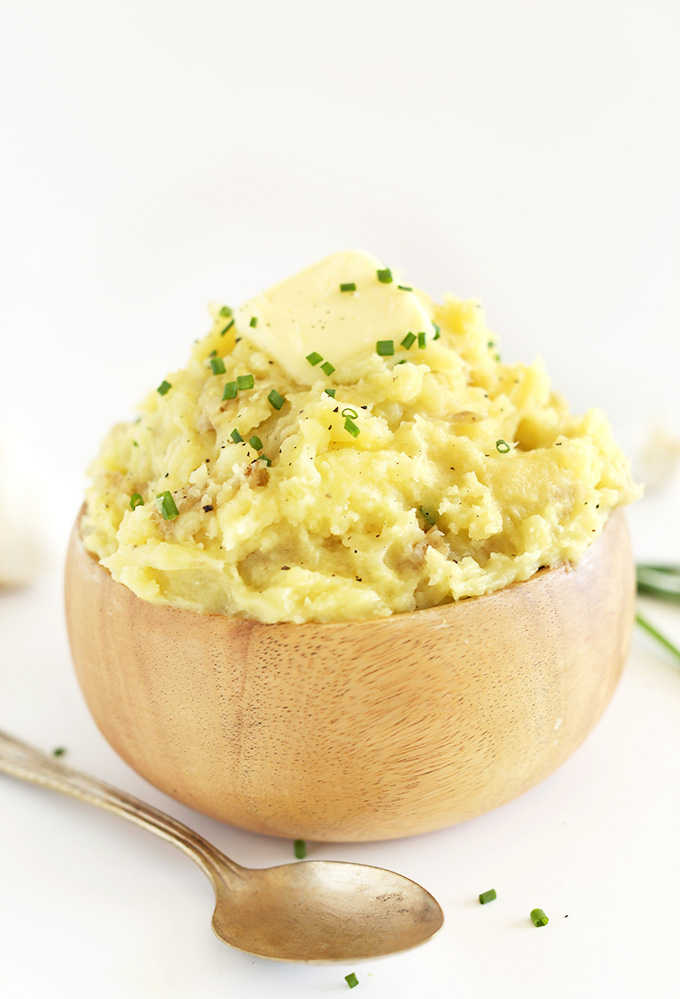 Wood bowl piled high with Vegan Mashed Potatoes topped with chives and black pepper