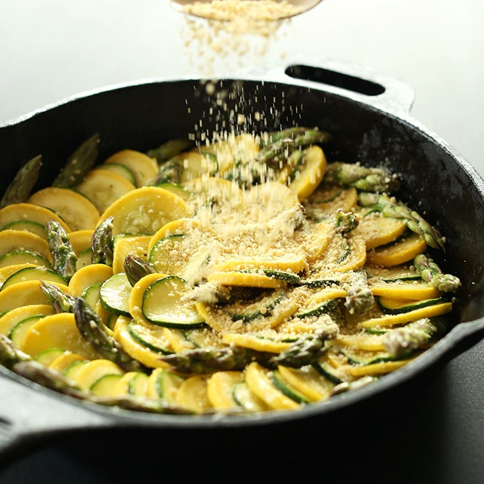 Adding a sprinkling of Vegan Parmesan Cheese to our Asparagus Zucchini Gratin recipe