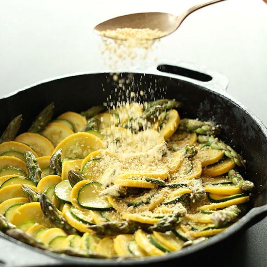 Sprinkling vegan parmesan cheese onto a skillet of Zucchini Gratin