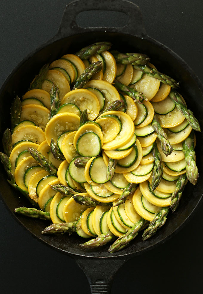 Cast-iron skillet filled with beautiful Vegan Zucchini Asparagus Gratin