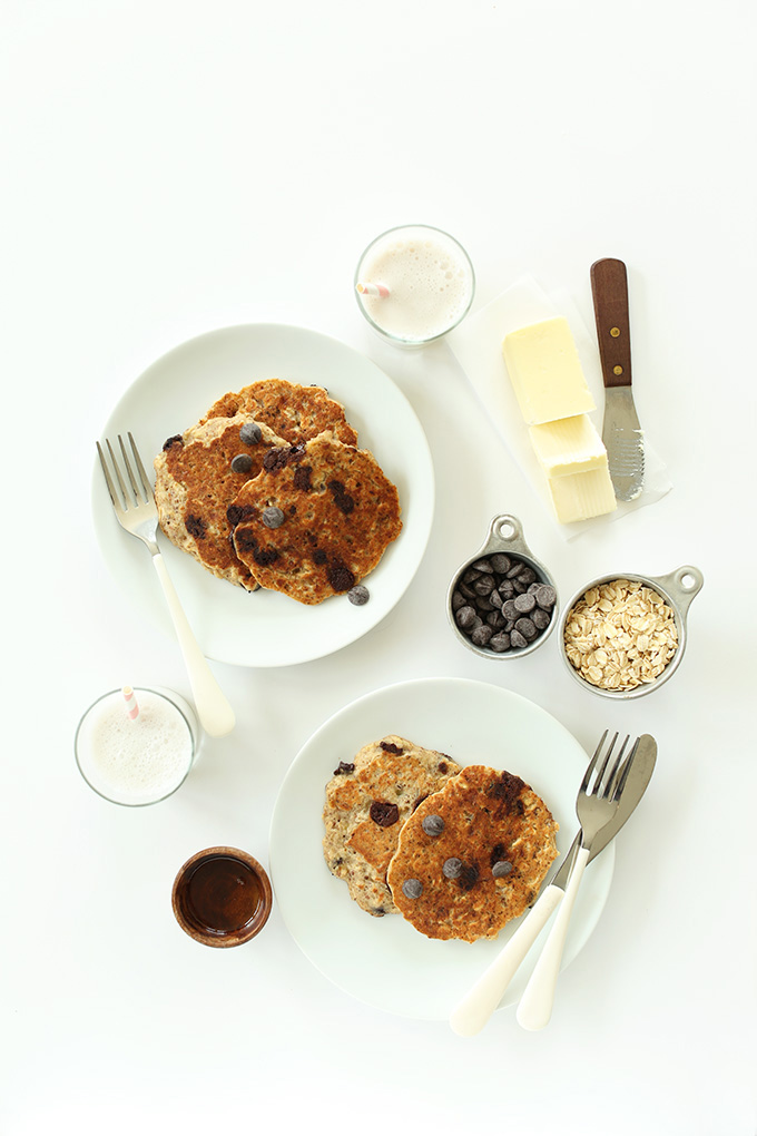 Two plates of GF Chocolate Chip Oatmeal Cookie Pancakes surrounded by ingredients used to make them