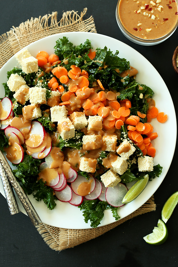 Plate of Thai Kale Salad made with radishes, tofu, carrots, and kale