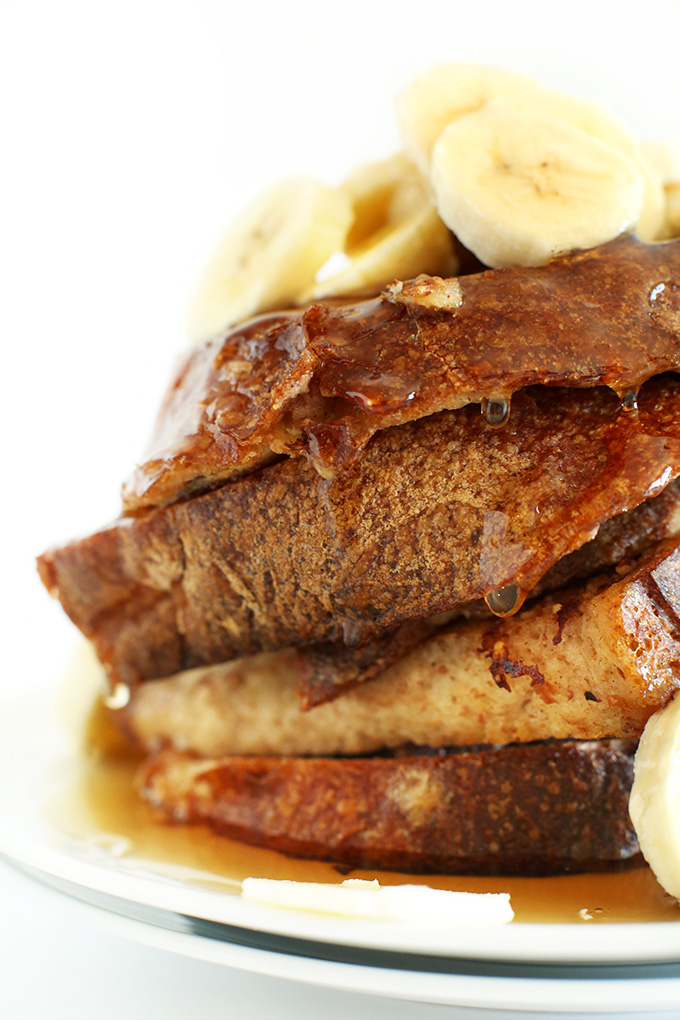 Stack of Vegan Banana French Toast with sliced bananas and maple syrup