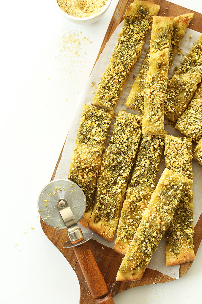 Cutting board with a batch of our Cheesy Pesto Vegan Breadsticks recipe