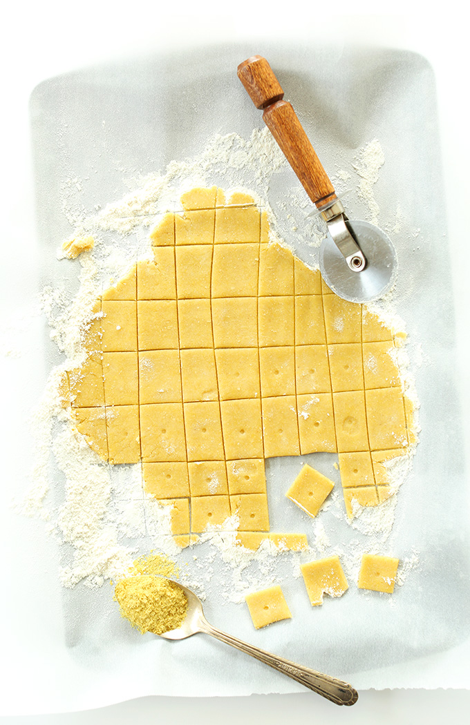 Using a pizza cutter to cut homemade Vegan Cheez Itz on a floured surface