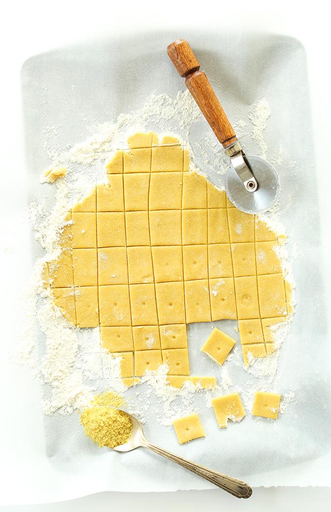 Using a pizza cutter to cut homemade Vegan Cheez Itz on a floured surface