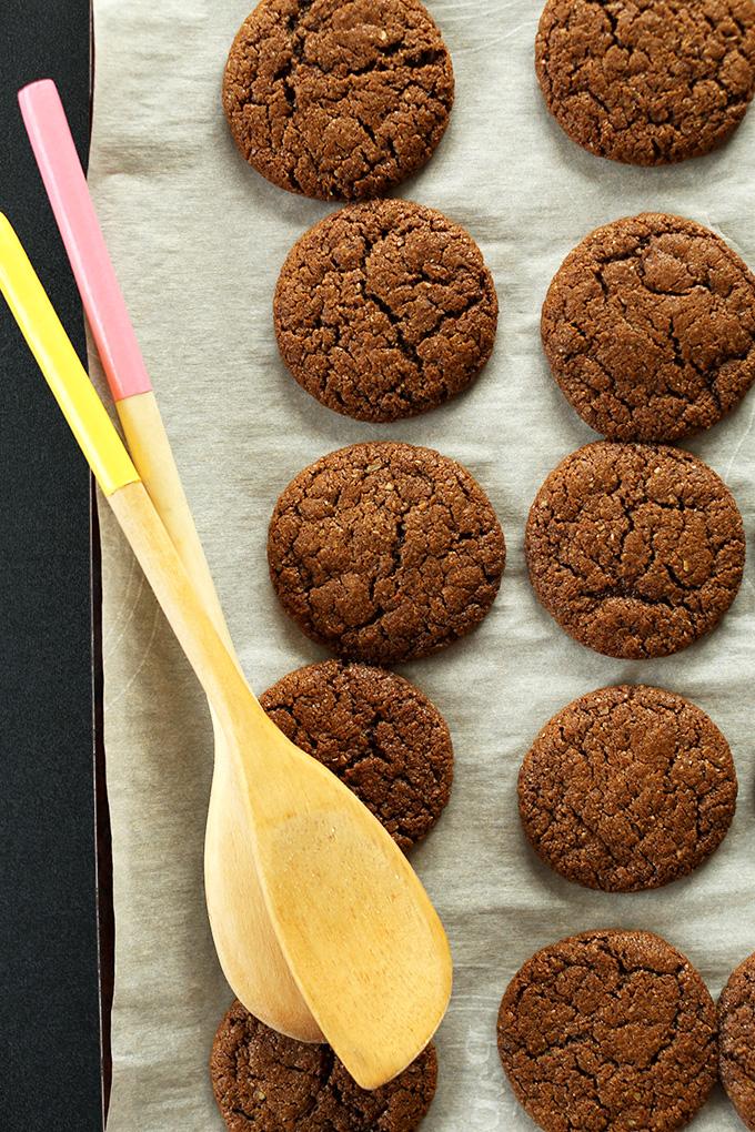 Bandeja para hornear forrada de pergamino rellena de galletas de jengibre veganas sin gluten