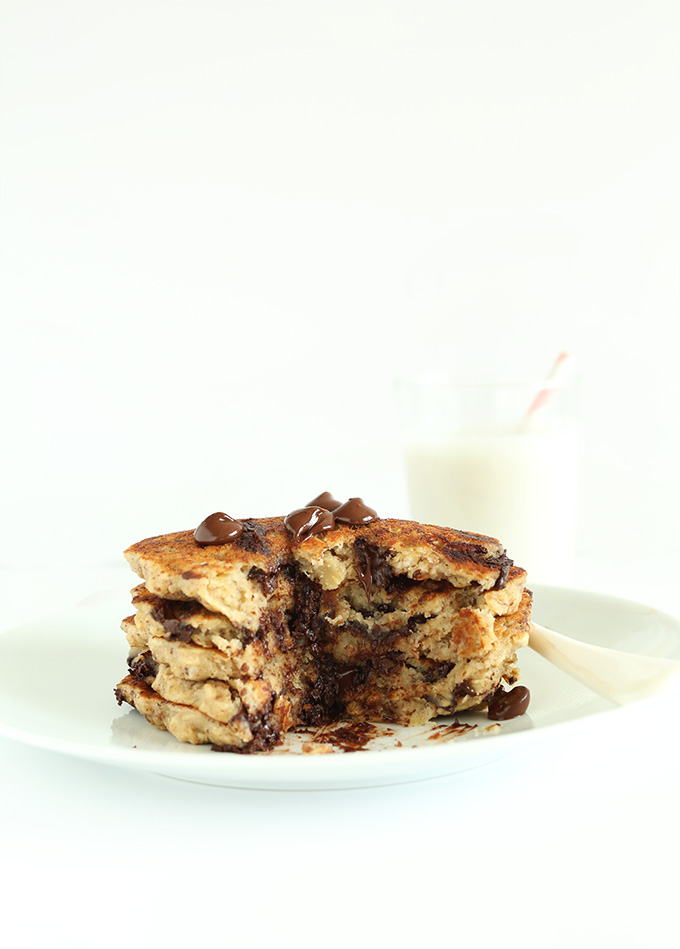 Partially eaten stack of gluten-free Oatmeal Cookie Pancakes topped with chocolate chips