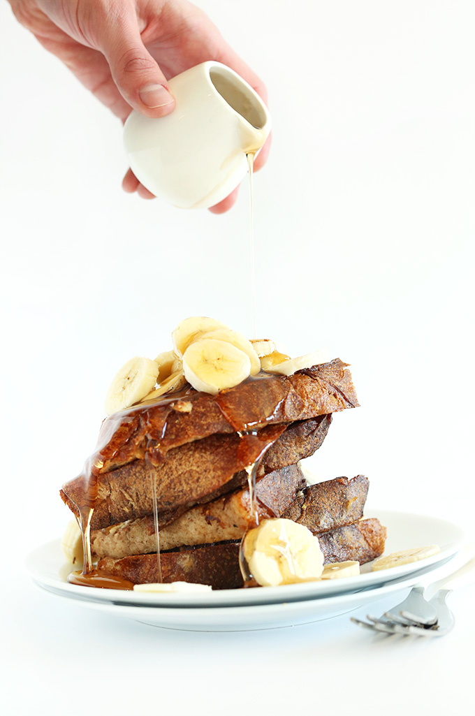 Drizzling maple syrup onto a stack of Vegan Banana French Toast