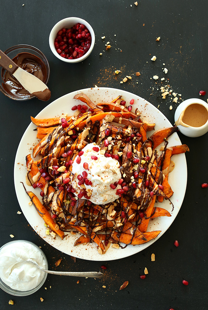 Big plate of Sweet Potato Superfood Dessert Fries topped with chocolate sauce, peanut butter and more