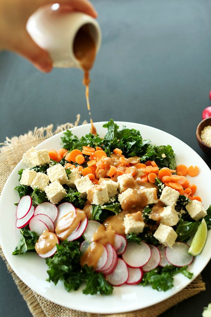 Pouring peanut dressing over Thai Kale Salad for a simple vegan gluten-free dinner