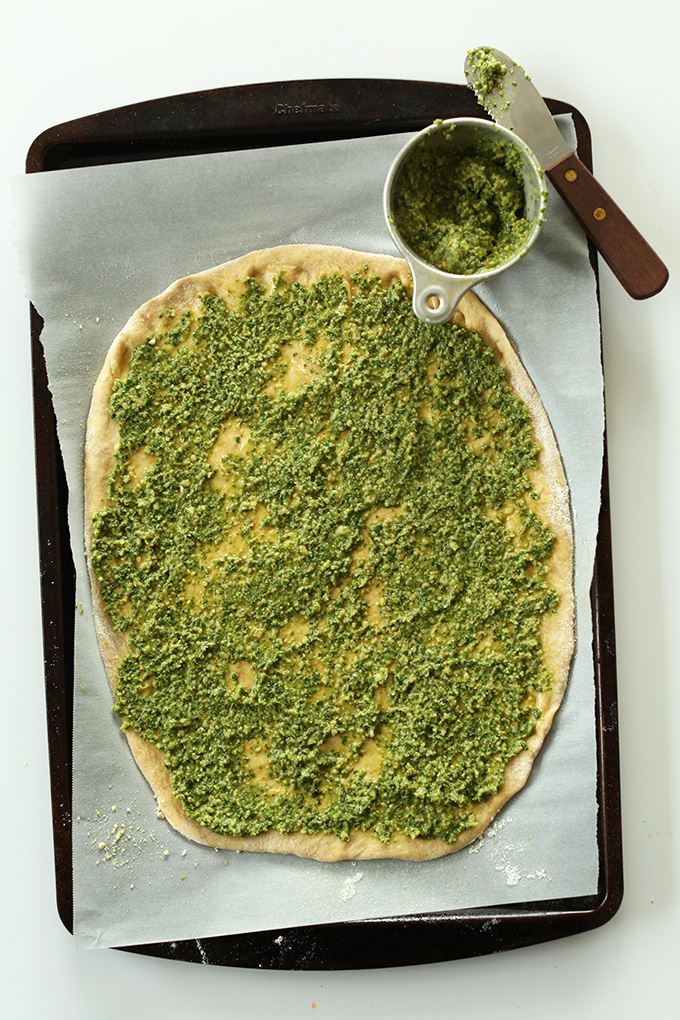 Parchment-lined baking sheet with vegan breadstick dough slathered with pesto