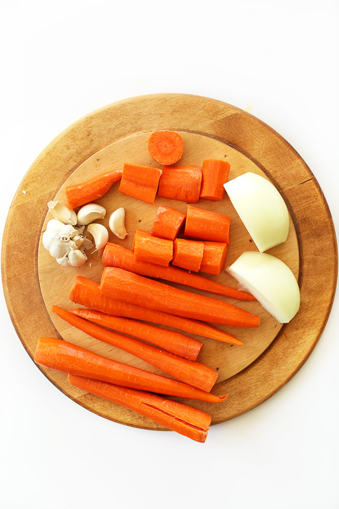 Cutting board with carrots, onion, and garlic for making delicious soup