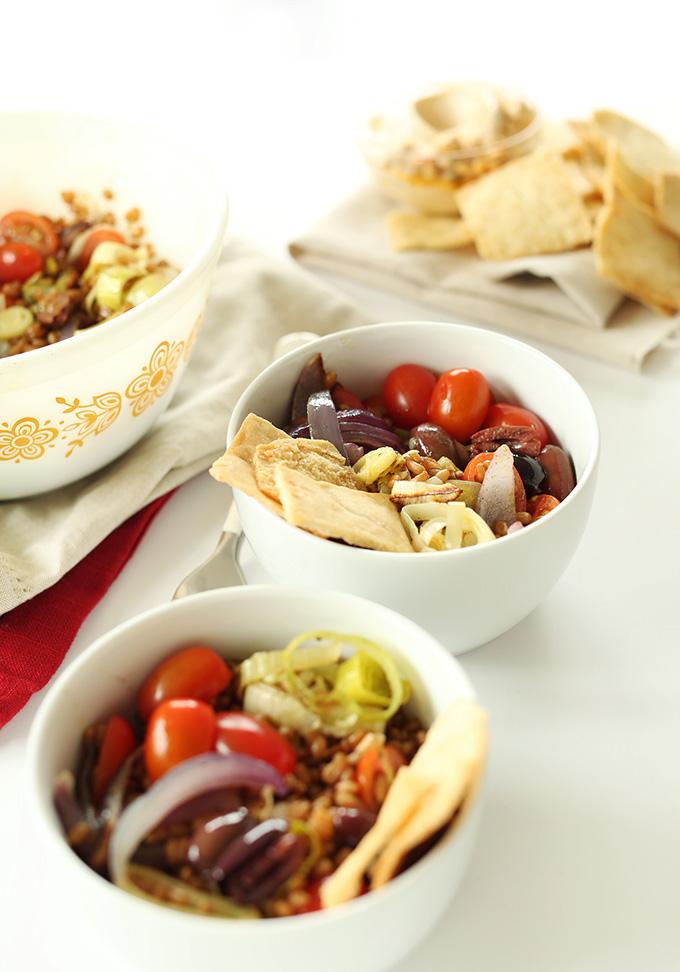 Bowls of Mediterranean Wheat Berry Salad alongside pita chips and hummus