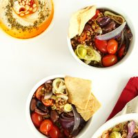 Two bowls of Mediterranean Wheat Berry Salad and a bowl of hummus
