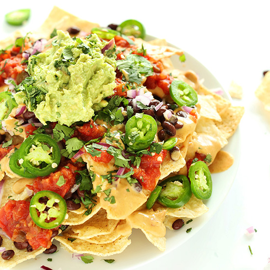 Plate of The Best Damn Vegan Nachos made with cashew queso, salsa, guac and more