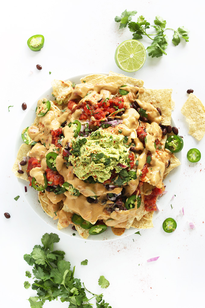 Plate of gluten-free vegan nachos piled high with queso, salsa, and guacamole