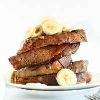 Slices of Vegan Banana French Toast piled high and topped with sliced bananas and syrup