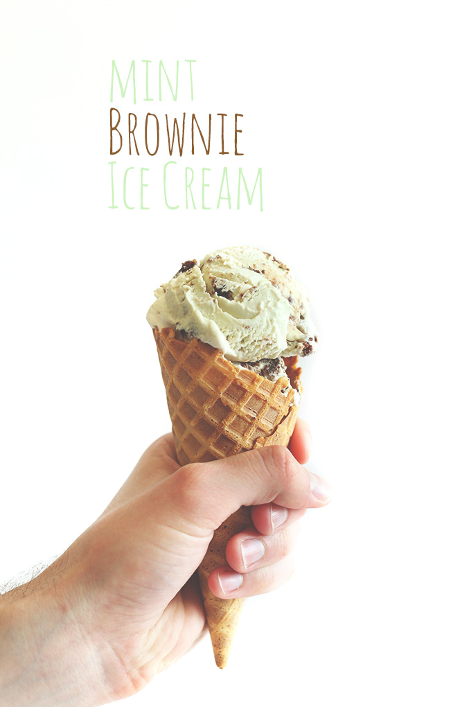 Holding up a waffle cone filled with scoops of Mint Brownie Ice Cream