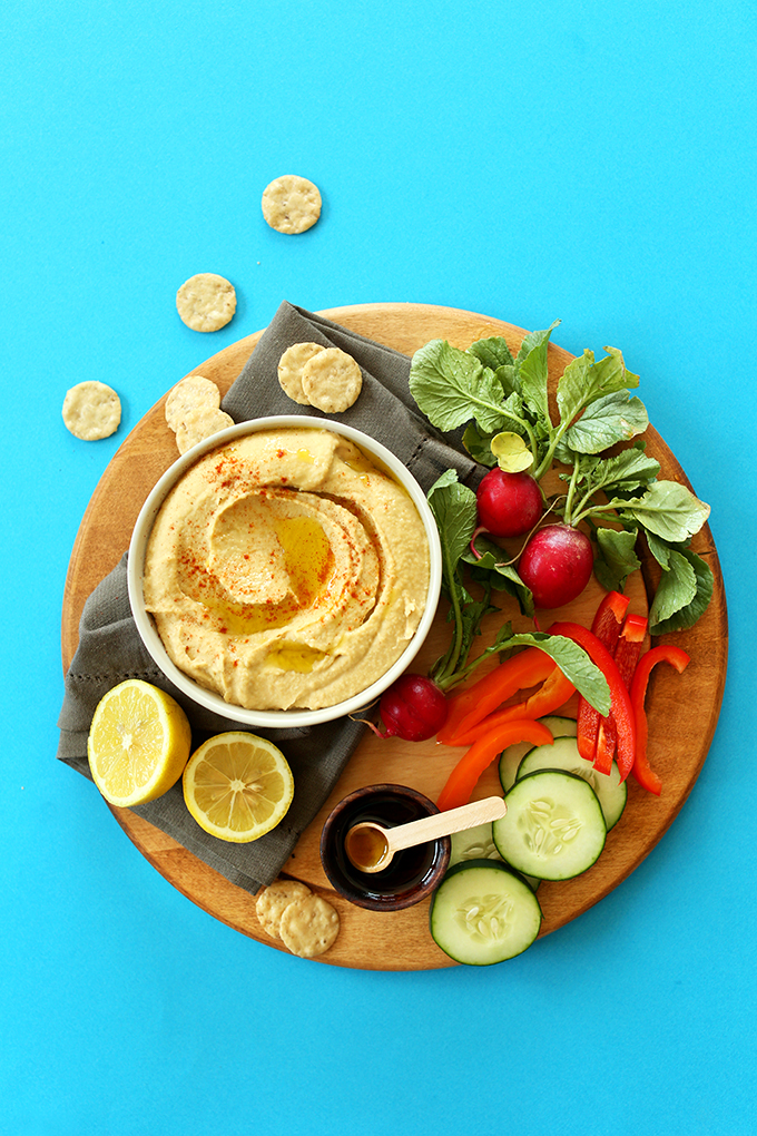 Bowl of our simple homemade Microwave Hummus on a cutting board of fresh vegetables