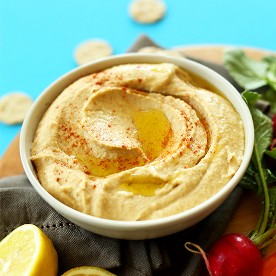 Bowl of homemade hummus topped with olive oil and paprika