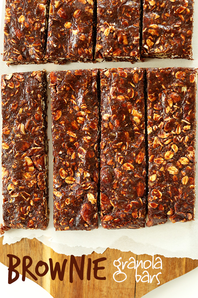 Freshly sliced homemade Brownie Granola Bars on a parchment-lined cutting board