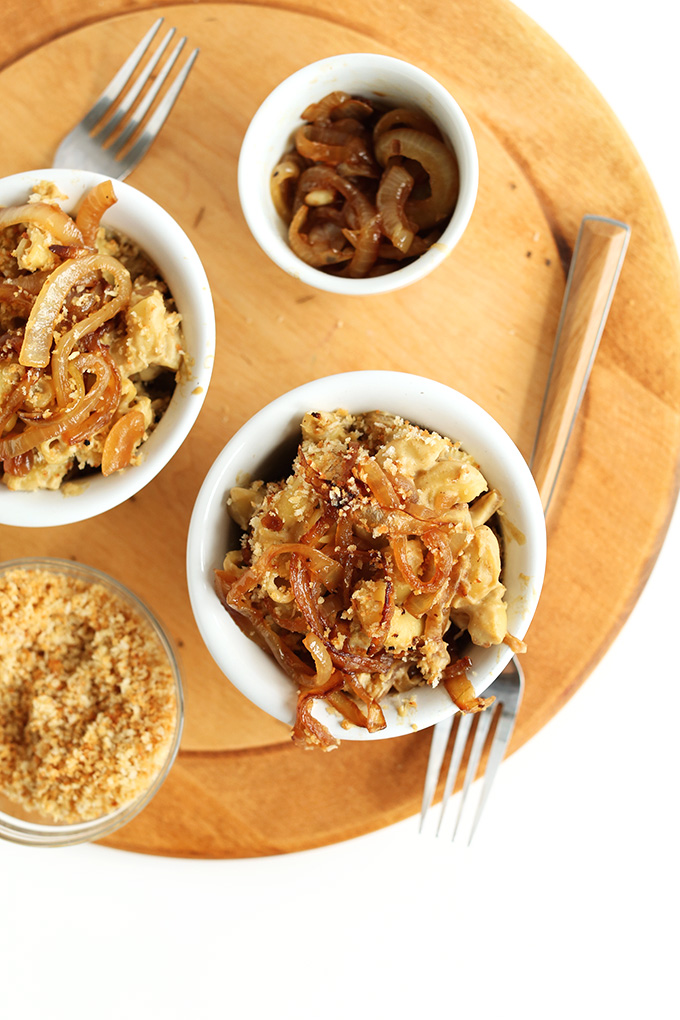 Bowls of Caramelized Onion Mac n Cheese with sides of breadcrumbs and extra caramelized onions