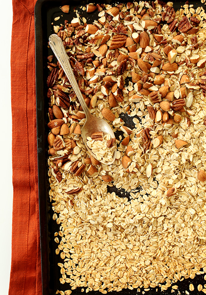 Baking sheet filled with oats, almonds, and pecans for making Healthy Brownie Granola Bars