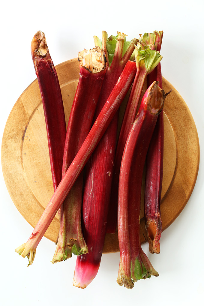 Stalks of fresh rhubarb on a wood cutting board