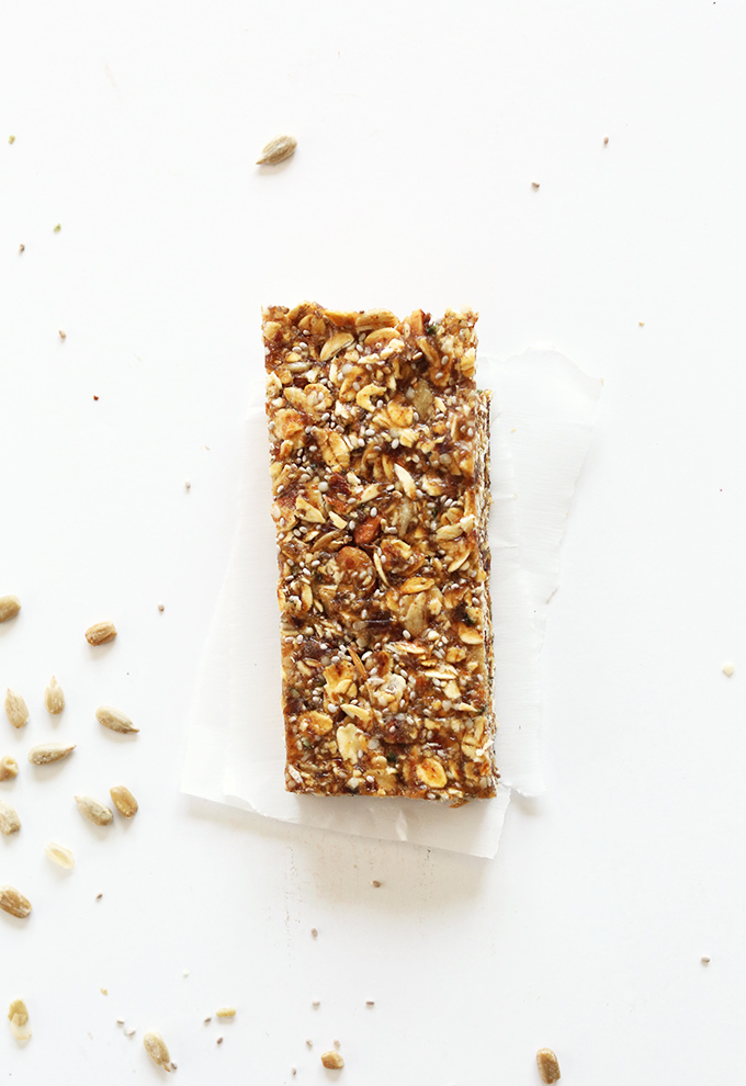 Vegan gluten-free granola bar resting on parchment paper on a white background