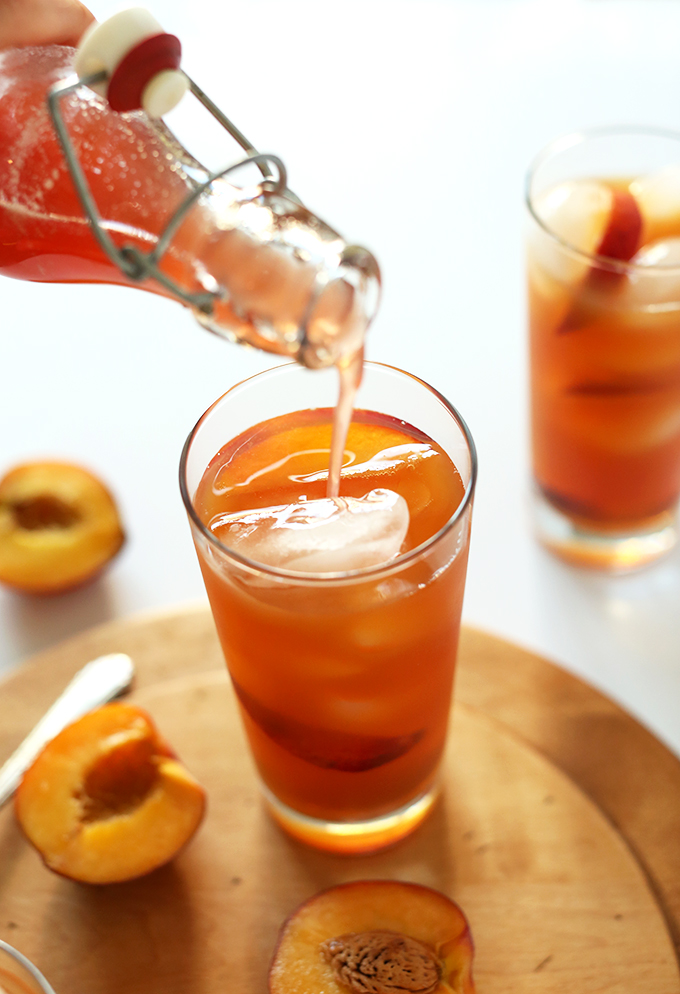Pouring Peach Iced Tea into a glass of ice cubes and peach slices