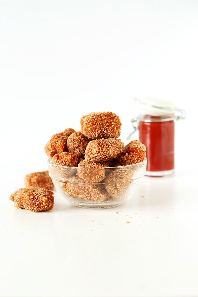 Bowl of Easy Vegan Sweet Potato Tater Tots and a spice jar filled with ketchup
