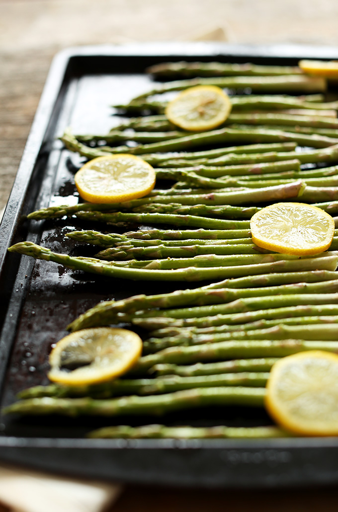 Baking sheet filled with asparagus and lemon slices ready to be roasted