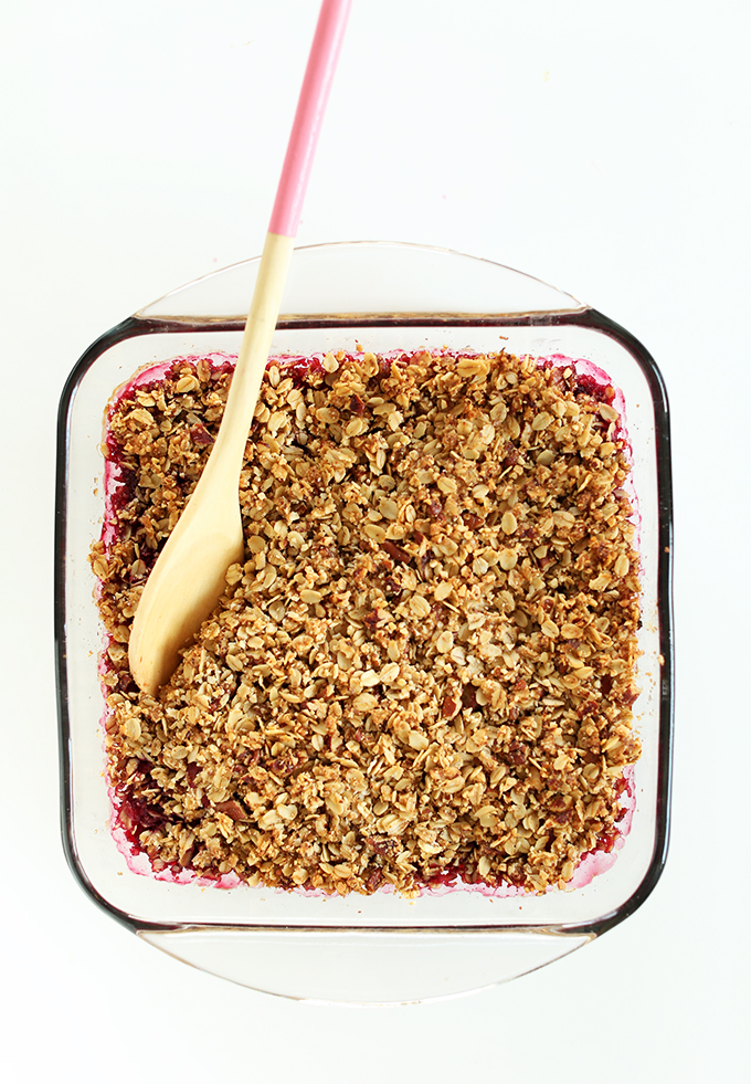 Using a wooden spoon to grab a serving of our Easy Vegan Raspberry Rhubarb Crisp