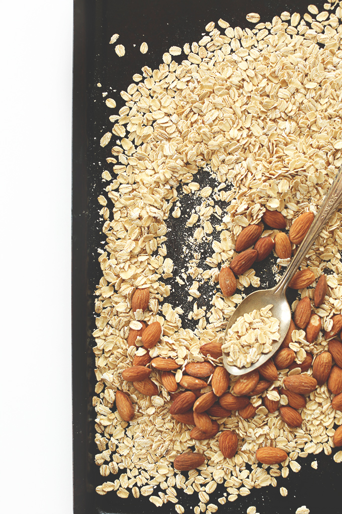 Oats and almonds on a baking sheet for making easy Super Seedy Granola Bars