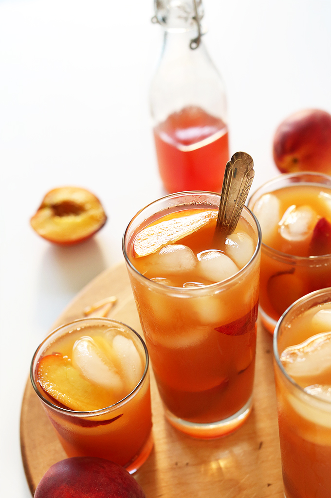 Fresh peaches and glasses of homemade Peach Iced Tea