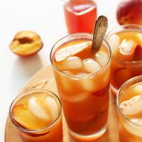 Glasses of our Perfect Peach Iced Tea with peach slices and ice cubes in them