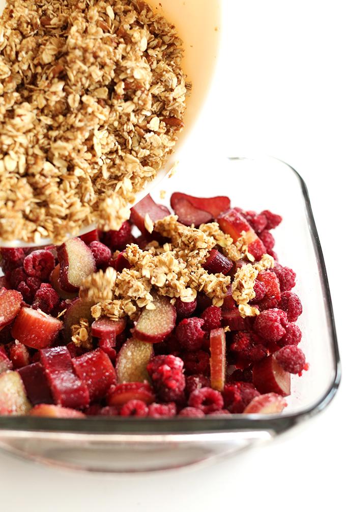 Pouring oat topping onto vegan Raspberry Rhubarb Crisp