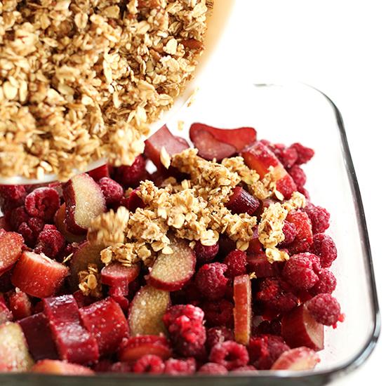 Spreading gluten-free crisp topping onto a baking dish of Vegan Raspberry Rhubarb Crisp