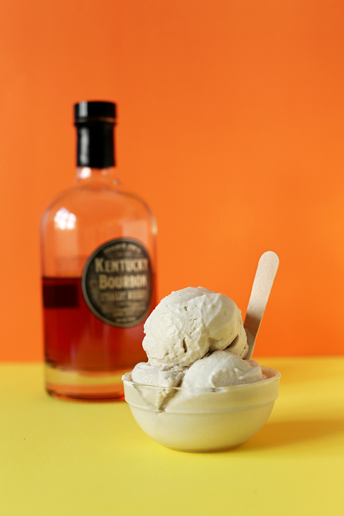 Bowl of Salted Bourbon Caramel Vegan Ice Cream with a bottle of bourbon in the background