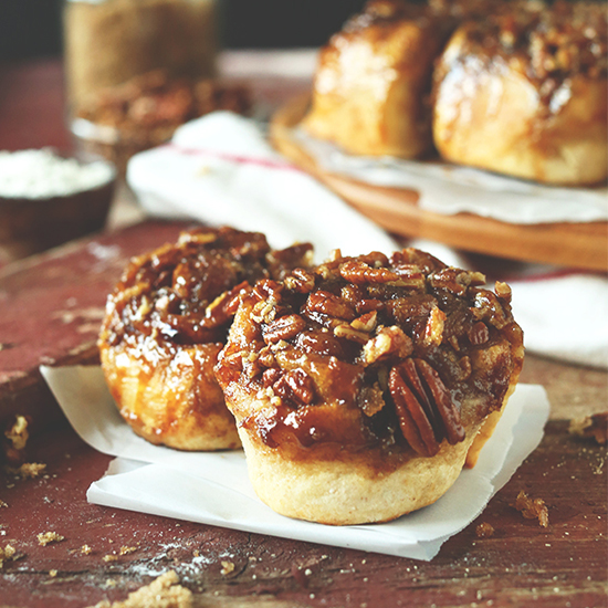 Two Vegan Sticky Buns on a piece of parchment paper