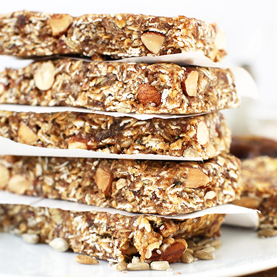 Tall stack of Super Seedy Granola Bars separated by pieces of parchment paper