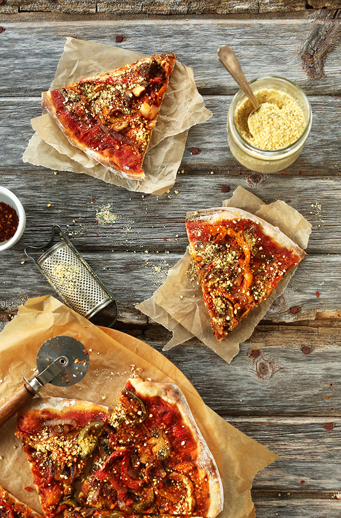 Slices of The Best Vegan Pizza alongside dishes of vegan parmesan cheese and red chili flakes