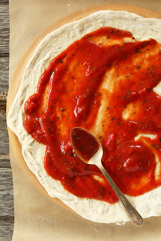 Using a spoon to spread pizza sauce onto dough for the Best Vegan Pizza