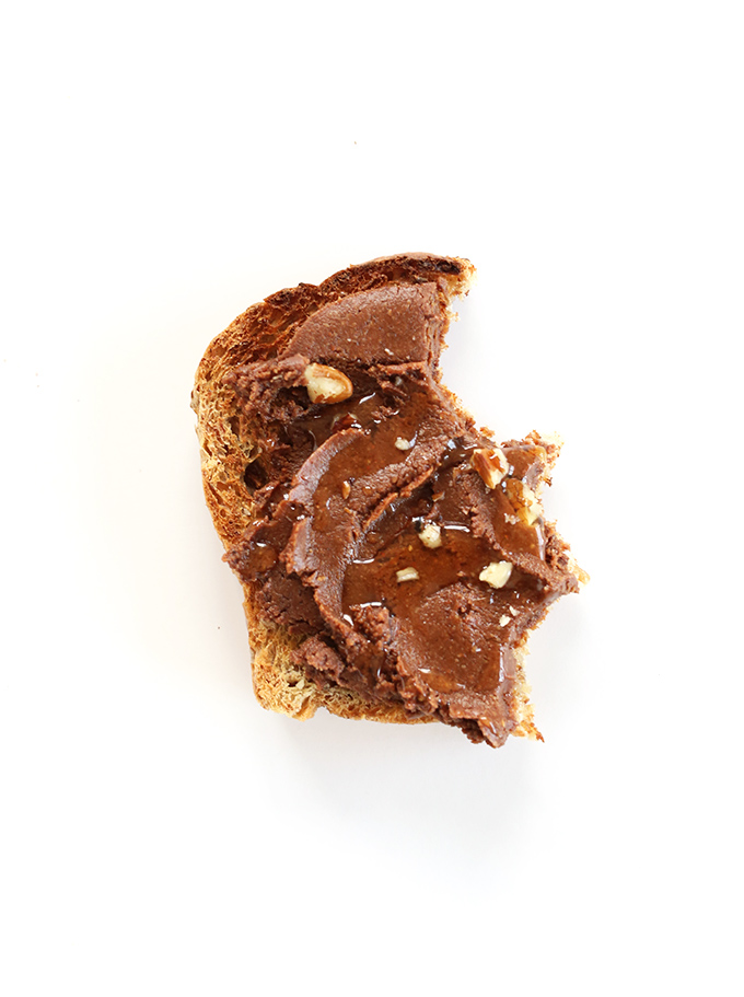 Partially eaten slice of gluten-free toast topped with Vegan Brownie Batter Spread