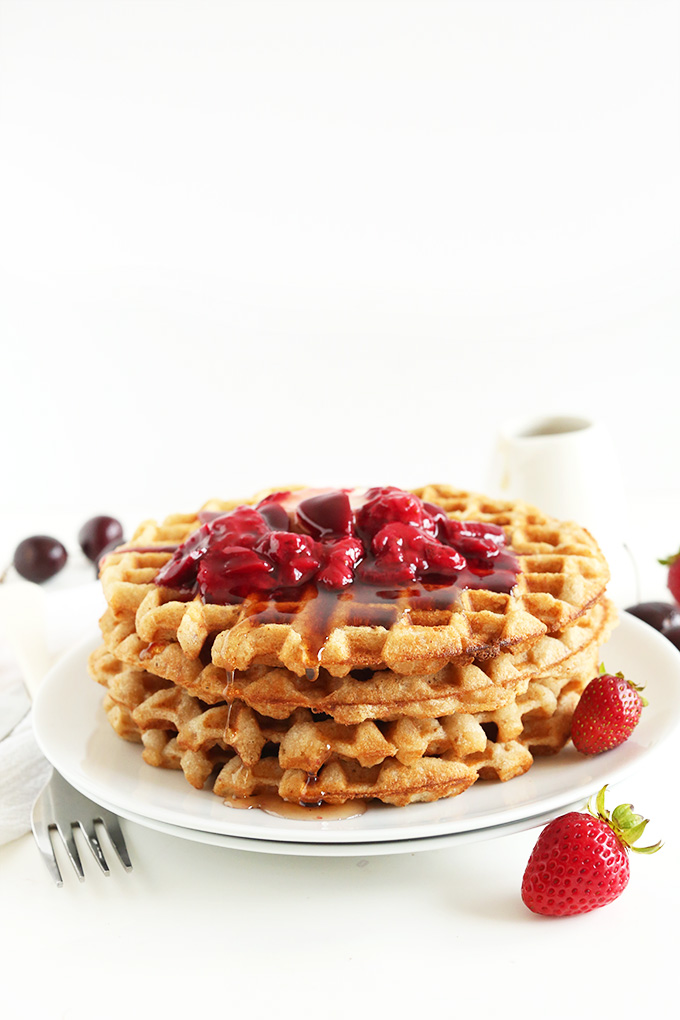 Stack of gluten-free oatmeal waffles with fruit compote and maple syrup