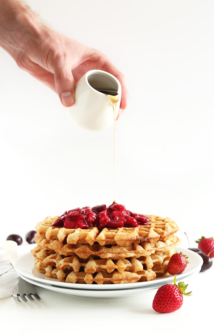 Drizzling maple syrup onto Vegan Gluten-Free Waffles topped with fruit compote