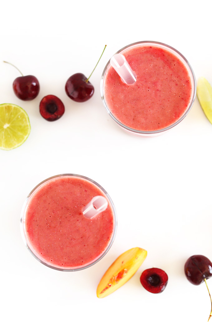 Glasses of our Cherry Limeade Smoothie with fresh cherries and limes